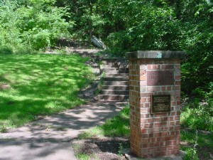 brick sign in front of a path surrounded by lawn and trees
